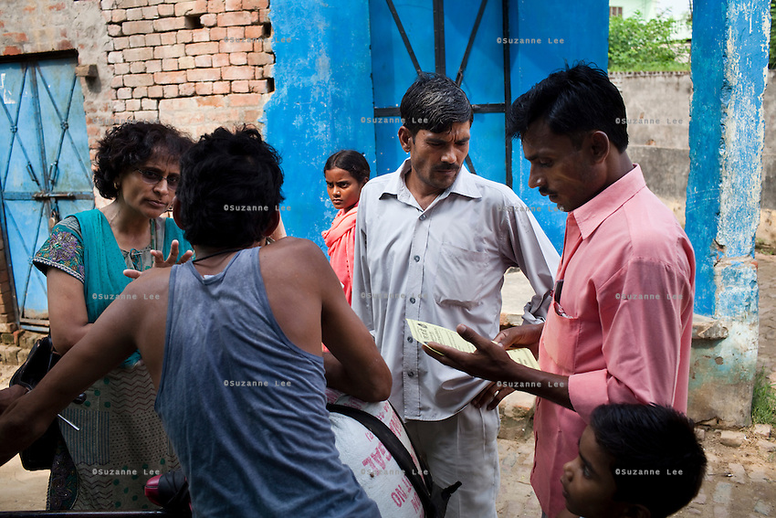 Jagroshan Sharma (aged 36, in grey) approaches random villagers from Shahpurjat village with Dr. Meenal Mehta (in blue), who is in charge of the USAID NSV projects in Ghaziabad, Uttar Pradesh, India. After doing NSV himself, he has been a star link worker introducing about 5 NSV cases per month since he started working part time under the tutelage of Dr Mehta. Jagroshan had chosen to do a non-scalpel vasectomy (NSV) for many reasons. He wanted to be an equal partner in the relationship, knew that NSV was less complicated and will not put his wife through numerous problems, and wants his two children to do well in life and study in English medium schools despite his modest earnings. Photo by Suzanne Lee / Panos London