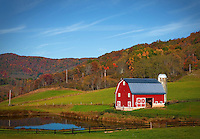 Bright Red Barn with pond and fall foliage in West Virginia Mountains