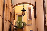 Looking down a narrow alley in Verona, Italy. A narrow alley in Verona, Italy with arches between buildings, balconies with plants, and lamps.