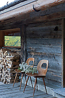 A pair of simple wooden chairs has been placed on the wooden decking at the door to the chalet