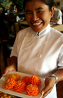 Thai cook proudly displaying her beautifully carved vegetables.  As with most world-class cuisines, the presentation of the food is almost as important as its taste and preparation.  A beautiful Thai smiles doesn't hurt in the presentation either.