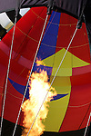 The flames of the burner to heat up a multi colored Hot Air Balloon