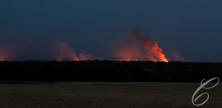 Smoke and flame from the Dyer Mill fire lights up the the  Grimes County, Texas horizon  east of Whitehall on June 20, 2011.