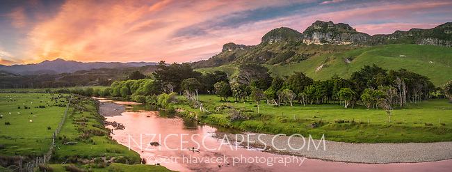 Purple colours of dawn over farmland at Paturau. Paturau River and limestone hills on west coast of South Island, Nelson Region, New Zealand