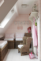 With the clever use of wicker furniture a cosy seating area has been created In a corner of a girl's bedroom