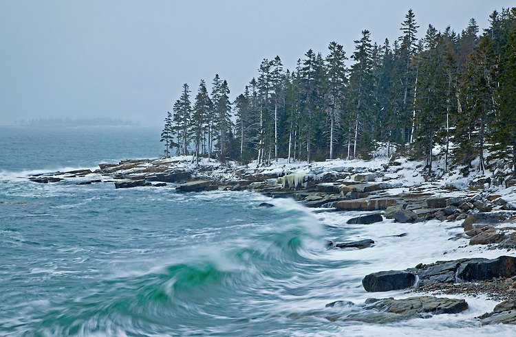 Waves crash into the eastern side of the Schoodic Peninsula during a winter snowstorm in Acadia National Park, Maine, USA