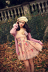 A pretty brunette in a pastel floral dress, white beret and lilac sweater posinh in an autumnal park.