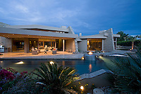 Dusk view of ultra modern home and pool