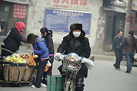 A man on an electric bicycle  wearing a mask in the streets of Lanzhou,  China.<br /> <br /> <br /> -------<br /> Lanzhou, in the Gansu province is the most polluted cities of China and in the world's top ten for atmospheric pollution due to human activity. The town is situated between two hills along the Yellow River and the polluted clouds remain blocked over the town. The sky is most of the time hidden by the pollution.