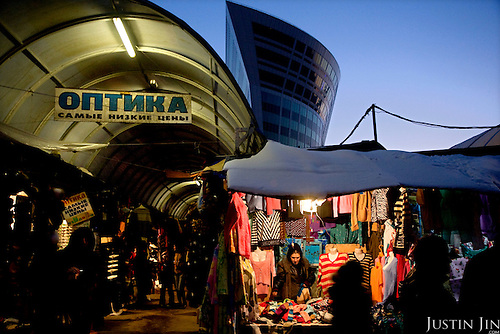 A garment hawker sells cloths in front of a modern building in Moscow, Russia.