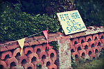 Old brick wall with bunting and sign to small summer fete in the village of Brome &amp; Oakley in Suffolk, England.