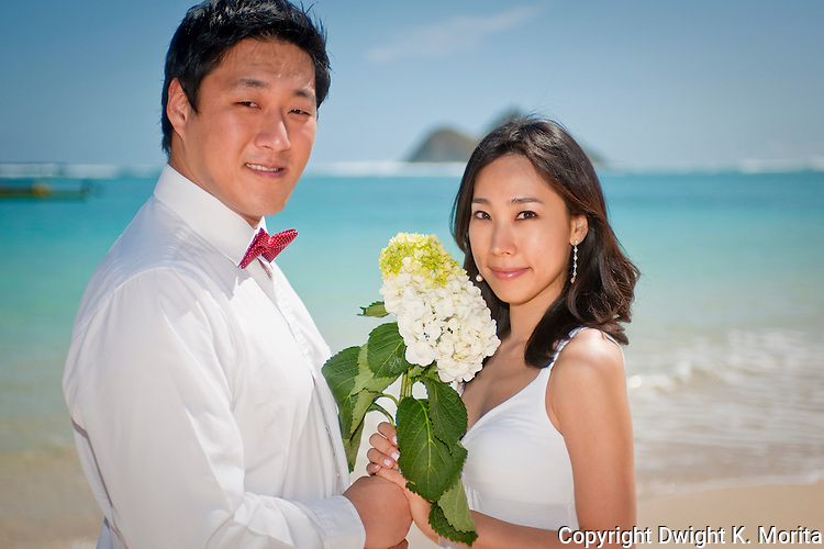 Asian bride and groom pose with bouquet on Lanikai beach as they look forward to their life as a married couple following their wedding.