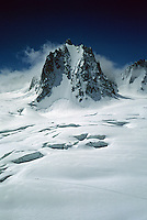 Dwarfed by the crevasses and peaks of the Mont Blanc Massif, four climbers snake their way across the valley atop the Alps between Courmayeur and Chamonix.