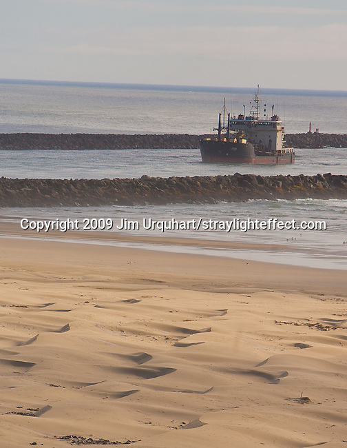 A commercial vessel makes it's way into the Harbor of Newport from the Pacific Ocean past the sandy beaches in Newport, Oregon. Jim Urquhart/straylighteffect.com 7/24/09