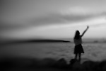 Woman standing on rocks at edge of water with one outstretched arm.