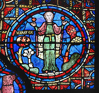 A woman wearing a long green dress and red cloak holds 2 red flowers in an attitude of prayer, perhaps giving thanks for the harvest, section of Virgo from the Zodiac and the labours of the months stained glass window, 1217, in the ambulatory of Chartres Cathedral, Eure-et-Loir, France. This calendar window contains scenes showing the zodiacal symbol with its corresponding monthly activity. Chartres cathedral was built 1194-1250 and is a fine example of Gothic architecture. Most of its windows date from 1205-40 although a few earlier 12th century examples are also intact. It was declared a UNESCO World Heritage Site in 1979. Picture by Manuel Cohen