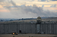 As smoke rises from Israeli airstrikes on Gaza, an Israeli army jeep patrols along the wall separating southern Israel from the Gaza strip. Israeli forces began an air offensive against Hamas in Gaza on 27/12/2008, which quickly escalated into an offensive by land, sea and air, in retaliation against Palestinian rockets fired into Israel. After eight days of bombardment, leaving over 400 Palestinians and four Israelis dead, Israeli tanks entered Gaza on 04/01/2009...