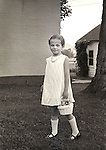 1968. Young girl ring bearer dressed for wedding with basket.