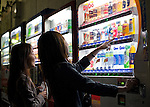 Customers buy drinks from vending machines in Tokyo, Japan on 25 April 2010. Photographer: Robert Gilhooly