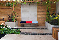 Garden bench against privacy wooden wall, with raised bed planters of flowers and perennials, trellis with climbing vines for vertical interest, calla lillies Zantedeschia planted in ground, with mixed media hardscaping of backyard patio