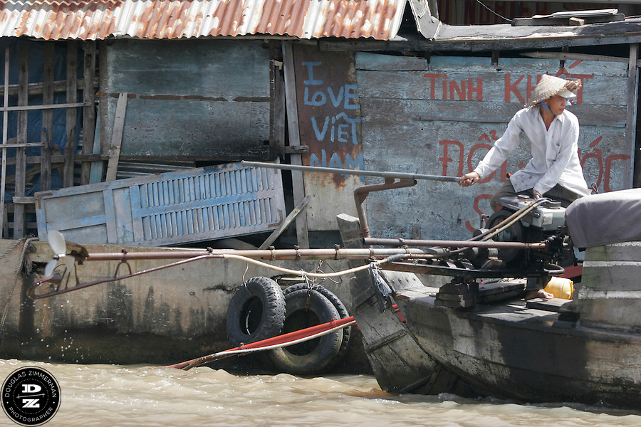 A boat pilot steers his motorboat away from a pier in the Cai Be Floating Market along the Mekong Delta in Vinh Long, Vietnam.  The Mekong Delta has long been the watery  throughfare for the many villages that dot the riversides of the delta. Many of the villages have floating markets where people can buy produce and other items from wholesalers.  Photograph by Douglas ZImmerman