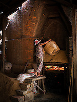 This 65 year old lady feeding the traditional Brick Kiln with rice husks near Can Tho, the hub of the Mekong Delta (Vietnamese: Đồng bằng S&ocirc;ng Cửu Long &quot;Nine Dragon river delta&quot;), also known as the Western Region (Vietnamese: Miền T&acirc;y or the South-western region (Vietnamese: T&acirc;y Nam Bộ) is the region in southwestern Vietnam where the Mekong River approaches and empties into the sea through a network of distributaries. The Mekong delta region encompasses a large portion of southwestern Vietnam of 39,000 square kilometres (15,000&nbsp;sq&nbsp;mi). The size of the area covered by water depends on the season.<br />