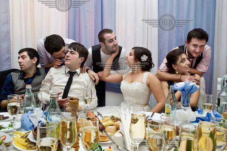 David and Nino (seated centre) at their wedding feast surrounded by friends and family.