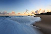Just before sunrise, white wash rushes onto shore at Secrets (or Secret) Beach, North Kaua'i.