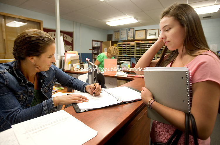 NAUGATUCK CT. 04 September 2013-090413SV04-From left, Jen Teixeira, main office secretary, signs in Nicole Kezelevick, 16, after she filed some first day of school paperwork at the High School in Naugatuck Wednesday. <br /> Steven Valenti Republican-American