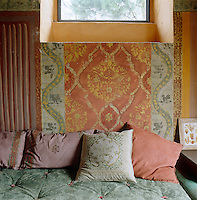 The patterns and colours of an ancient and intricately painted wall of this Tuscan living room have been sensitively echoed in the choice of fabrics