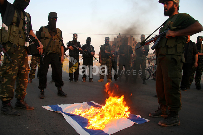 """Palestinian militants of the military wing of the popular resistance committees """"El-Nasser Salah El-Deen brigades"""" burn the Israeli Flag during  a protest calling for lift the siege on Gaza, in Deer El-Balah town Central Gaza Strip."""