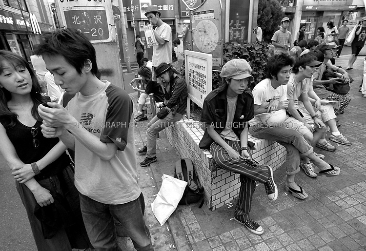 "8/10/2002--Shimokitazawa, Tokyo, Japan..Too cool for school--Japanese college students hang out in Shimo's main plaza, waiting to meet friends and start an evening out...Wedged between Tokyo's Shinjuku and Shibuya wards, Shimokitazawa's maze of narrow streets form the ramparts of all that is non-conformist in get-along, go-along Japan. In ""Shimokita,"" old village shops trade happily beside newer, eccentric clothing stores, funky restaurants, matchbox playhouses and live-music clubs. The unpretentious ambience is a magnet for students and other young visitors for whom Tokyo's usual street fashion scene has become more fascist than fun and mainstream entertainment is, well, too mainstream. Musicians, designers, aspiring actors and other would-be iconoclasts have settled the area, as have young professionals opting for a less-structured lifestyle. ...All photographs ©2003 Stuart Isett.All rights reserved.This image may not be reproduced without expressed written permission from Stuart Isett."