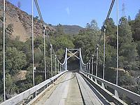Wooden suspension bridge over river.