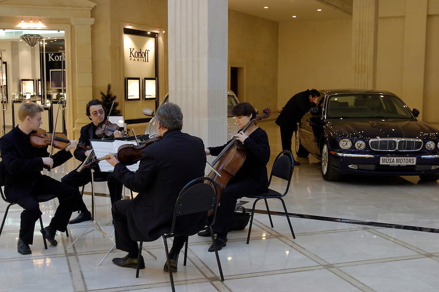 Moscow, Russia, 04/01/2004..A string quartet plays while a man inspects a Jaguar car at the luxurious but largely deserted Crocus City shopping mall.