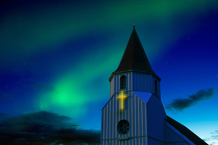 Church with a glowing cross and the Northern lights playing in the sky