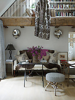 A high-backed sofa has been placed beneath the beamed mezzanine floor in the double-height living area