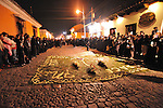 """During colorful and festive """" Semana Santa"""" (Saints week) in Antigua, Guatemala the streets are filled day and night with endless processions of people draped in robes, carrying massive coffins with effigies of  the crucified Jesus Christ.  The floats weigh up to 7,000 pounds with 50-100 curcuruchas or carriers bearing their weight.  Funeral marching bands follow the floats, announcing themselves with sounds of slowly beating drums, clapping cymbals and deep-throated tubas. Thick incense creates a haunting, ghost-like fog. Crowds hush as the solemn procession passes by.  ..Antigua, a colonial town, is a UNESCO World Heritage site."""