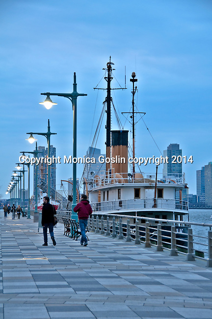 Historic boats, open for tours, sit along the Hudson River, just off of the Hudson River Greenway pedestrian walk in New York City, with Jersey City skyline in the background; sunset on the Hudson