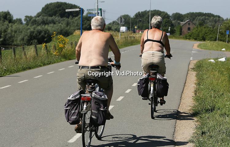 Foto: VidiPhoto<br /> <br /> DODEWAARD - Zoek de verschillen. Met deze hitte doen mensen vreemde dingen om toch wat af te koelen. De vrouw van dit fietsende echtpaar op de dijk bij Dodewaard maandag, doet niet onder voor de blote bast van haar fietspartner. Met alleen een BH als bovenstuk fietst ze nogal gewaagd in de brandende zon dwars door de Bijbelgordel.