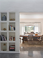 Deep shelving is built in to one side wall of the large open doorway that leads from the living to dining room
