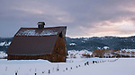 Idaho, West Central, New Meadows. An old barn in the morning light of winter in a snow covered landscape.