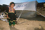 An Afghan refugee girl in front of her family's tent in Shamshatoo refugee camp..