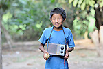 A boy walks with his radio in Las Flores, Ixcan, Guatemala.