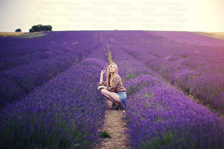 A young woman alone outdoors in summer crouching in a lavender field