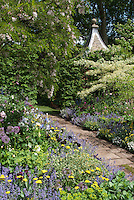 Garden stone path walkway through lush flowering garden with lots of different flowers, gazebo roof, wisteria vine