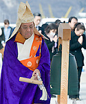A Buddhist priest strikes the bell of hope during a ceremony to mark the one year anniversary of the disasters in Ofunato, Iwate Prefecture, Japan on 11 Mar 2011. .Photographer: Robert Gilhooly