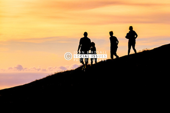 A family seen in silhouette as a spectacular sunset breaks over the coast in Newquay, Cornwall.