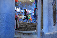 Young girl walking past a shop display at the top of a narrow stepped street painted blue in the medina or old town of Chefchaouen in the Rif mountains of North West Morocco. Chefchaouen was founded in 1471 by Moulay Ali Ben Moussa Ben Rashid El Alami to house the muslims expelled from Andalusia. It is famous for its blue painted houses, originated by the Jewish community, and is listed by UNESCO under the Intangible Cultural Heritage of Humanity. Picture by Manuel Cohen