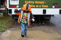 4 year old Marshall plays in a puddle as his grandmother picks up groceries from a food distribution in his rural trailer community. Marshall and his grandmother were able to bring home bread, juice, potatoes and many other groceries. Eastern Tennessee: Food is delivered to a remote trailer community where unemployment leaves most residents with food insecurity. Families are often forced to choose between heating their mountain homes or purchasing food.