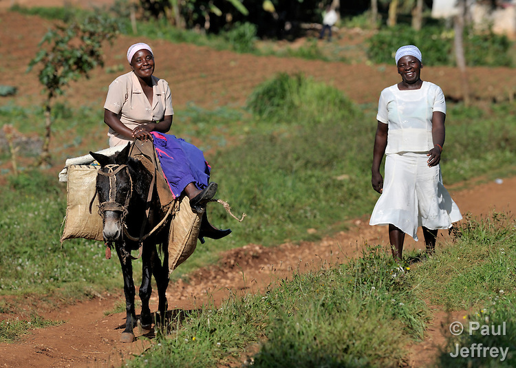 In the Haitian village of Foret des Pins, a woman rides a donkey while her friend walks along.